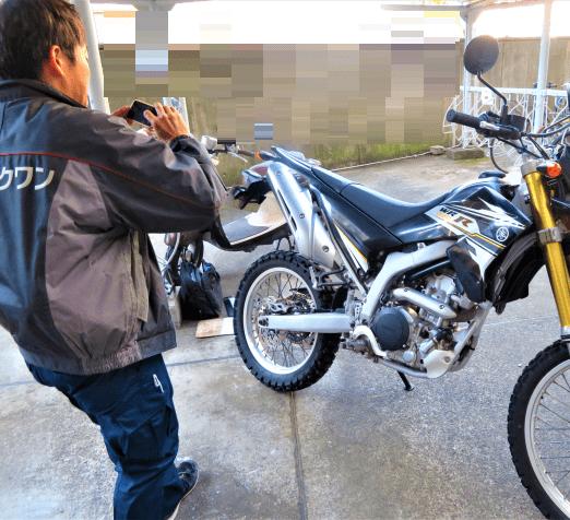 バイクワンの担当者でスマホでバイクの写真を撮影してる画像